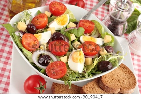 Chef's salad including lettuce, cherry tomatoes, onion, olives, cheese and egg with wholemeal bread.