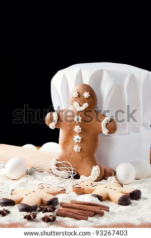 Chef's toque, gingerbread man and food ingredients over black background