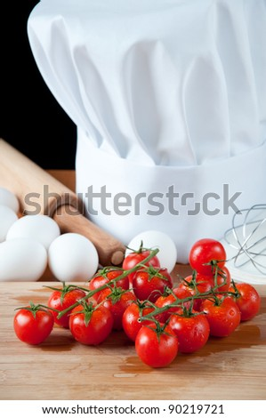 Chef's toque or hat with fresh tomatoes, eggs and kitchen utensils