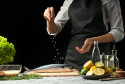 Chef salting mackerel fish on a black background