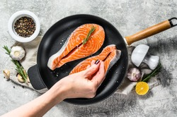 Chef salts raw salmon steak in a frying pan. Healthy seafood. Gray background. Top view. Space for text.