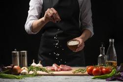 Chef salts steak grill pan. Preparing fresh beef or pork. Horizontal photo with a dark black background.