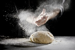 Chef scattering flour while kneading dough for bread
