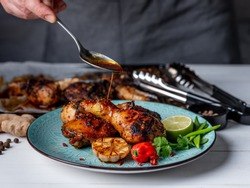 Chef serving baked chicken with forceps on blue plate.