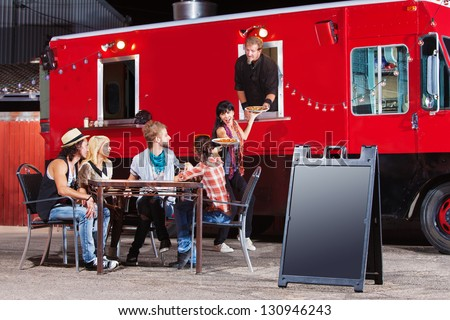 Chef serving food at mobile restaurant with blank sign
