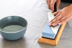 Chef sharpening knife on table. Japanese setting with asian woman. With water bowl.