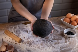 Chef showing a portion of fresh dough with sepia addition for black dumplings. Cooking dumplings – step by step guide.
