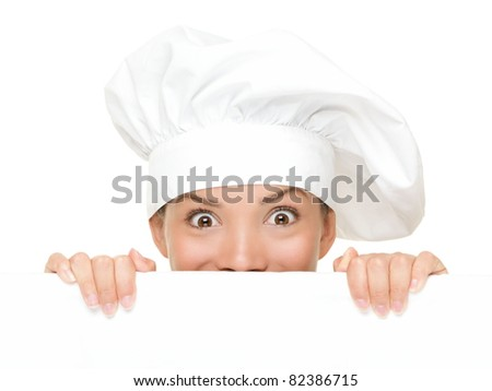 Chef Sign. Woman cook / baker looking over paper sign billboard. Surprised and funny expression on young Asian / Caucasian woman isolated on white background. - stock photo