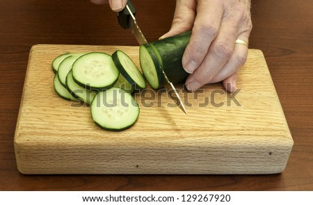 chef slices a cucumber on a small cutting  board