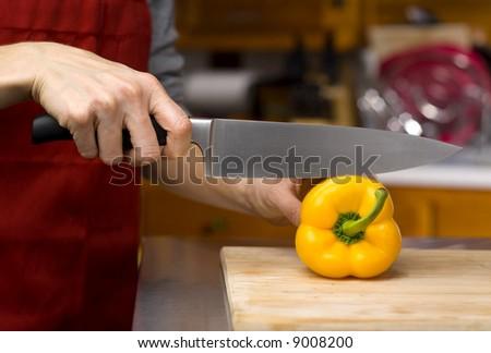 chef slicing fresh yellow pepper
