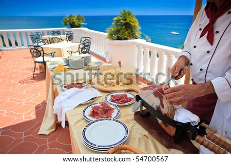 "Chef slicing ""Parma ham"" on wedding buffet on a beautiful terrace overlooking the sea"