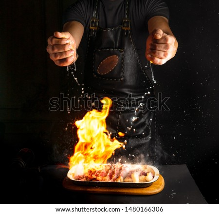 Chef sprinckles lemon juice on flambe meat while cooking a dish. Low key image. Stock photo ©