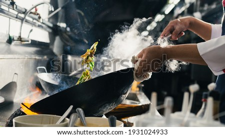 Chef stir fry busy cooking in kitchen. Chef stir fry the food in a frying pan, smoke and splatter the sauce in the kitchen. Zdjęcia stock ©