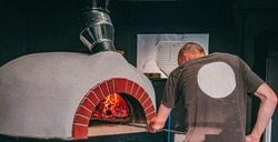 chef takes pizza. Italian pizza is cooked in a wood-fired oven