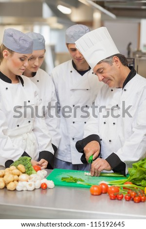 Chef teaching cutting vegetables to three trainees in the kitchen