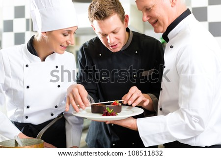 Chef team in restaurant kitchen with dessert working together