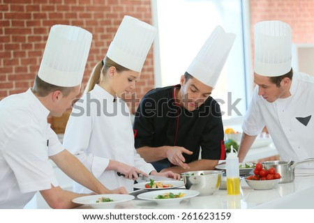 Chef training students in restaurant kitchen Stock photo ©