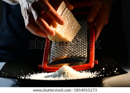 chef while grating some Parmesan cheese into a plate Foto d'archivio ©