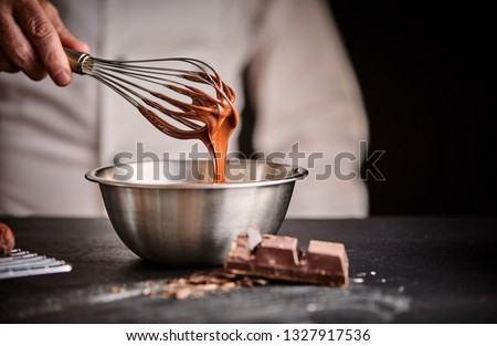 Chef whisking melted chocolate in a stainless steel mixing bowl using an old vintage wire whisk in a close up on his hand