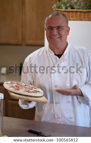 chef with frozen pizza in kitchen presenting
