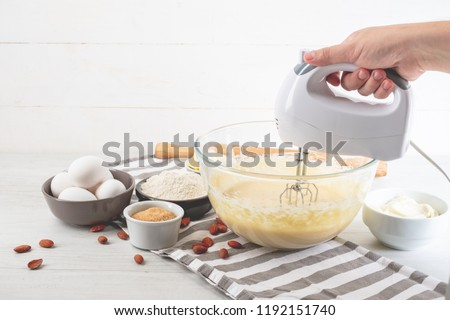Chef with mixer in hands cooking sweet cheesecake with cooking ingredients on kitchen table white background.