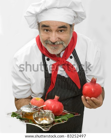 chef with poganate, ripe  fresh apple with honey for rosh hashana