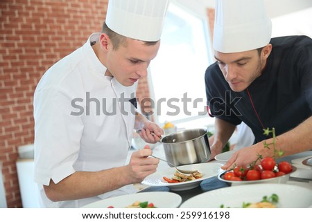 Chef with young cook in kitchen preparing dish Stock photo ©