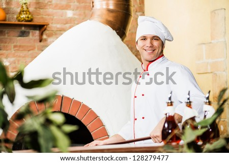 chef working in the kitchen near the fiery furnace, traditional cooking