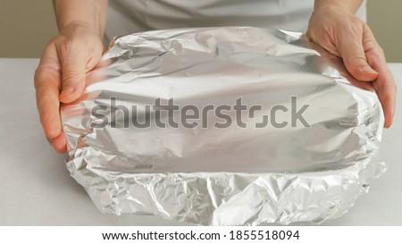 Chef wraps baking pan with aluminum foil. Baking process