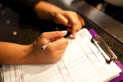 Chef writes down the temperatures of the fridges on the temperature check list,