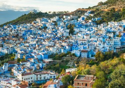 Chefchaoeun blue city in Morocco panoramic view on sunset with blue houses and green hills around with soft focus