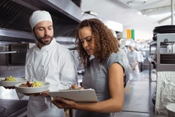 Chefs discussing menu on clipboard in commercial kitchen