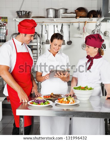 Chefs looking for recipe on a digital computer while cooking at kitchen