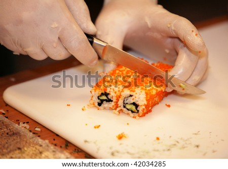 CHELYABINSK ? NOVEMBER 17: Sushi master class, Holiday Inn Chelyabinsk-Riverside 4*. Gloved hands cutting rolls with knife