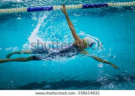 Chelyabinsk, Russia - October 21, 2015: young beautiful girl swims backstroke during Championship of Chelyabinsk swimming