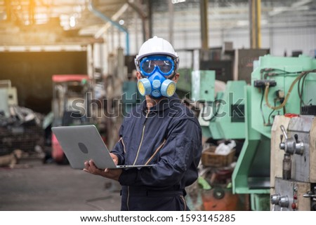 Chemical engineers wear helmet hat, and put chemical-resistant masks, carry laptops, inspect and control chemicals in the factory.