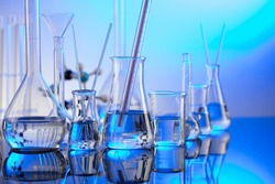 Chemical experiment concept. Laboratory equipment. Blue background.