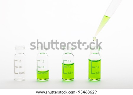 Chemical experiment: Sample vials for chromatography filled with different volumes of green liquid and a pipette tip with a droplet. Isolated on white, clipping path included