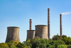 Chemical factory chimney. Heavy industry plant near green forest, with blue sky above.