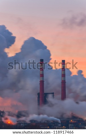 Chemical factory in the morning, with pipes and polluting smoke, long exposure