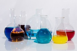 Chemical flasks with multi-colored liquid on a white background, reagents for experiments