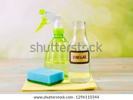 Chemical free home cleaner products concept. Using natural destilled white vinegar in spray bottle to remove stains. Tools on wooden table, green bokeh background, copy space. Foto stock ©