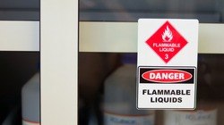 Chemical hazard sign pictogram, Globally Harmonized System of Classification and Labelling of Chemicals (GHS). Flammable liquid danger warning caution sticker with container bottle in storage cabinet.