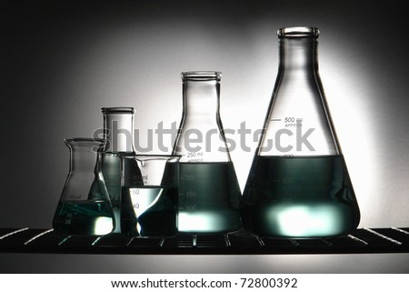 Chemical laboratory glassware with glass conical Erlenmeyer flasks and a scientific beaker with green chemistry liquid on a wire shelf for an experiment in a science research lab