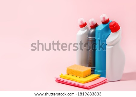 Chemical poisoned cleaning supplies bottles isolated on pink pastel background. Hard shadow, trendy shot, copy space for your adds, cleaning service flyer, coupon, banner