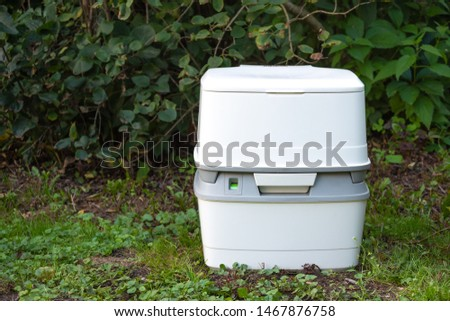Chemical portable toilet. Single portable toilet standing on a green meadow  #1467876758