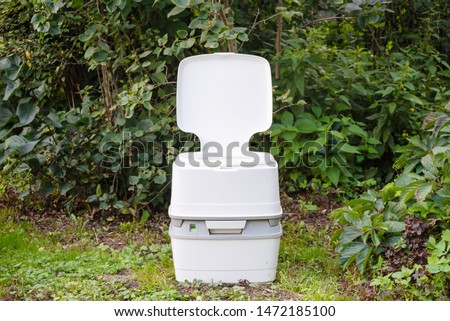 Chemical portable toilet. Single portable toilet standing on a green meadow  #1472185100