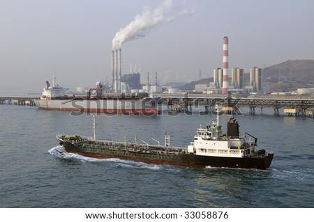 Chemical/power plant air pollutions with white clouds of smoke, crude oil tanker, disharging on front