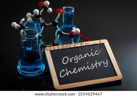 Chemical reaction, science class and STEM concept with a model of a molecule on chemistry glassware and flasks filled with blue liquid and a chalkboard with organic chemistry written on #1014629467