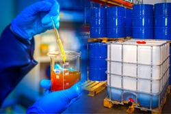 Chemical research at the enterprise. Chemist with samples of the substance on the background of barrels and container. Product quality control. Quality of raw materials for production.